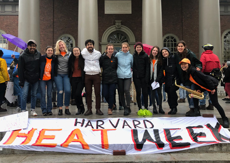 "Young campus fossil fuel divestment activists pose with a banner that says ""Harvard Heat Week""."