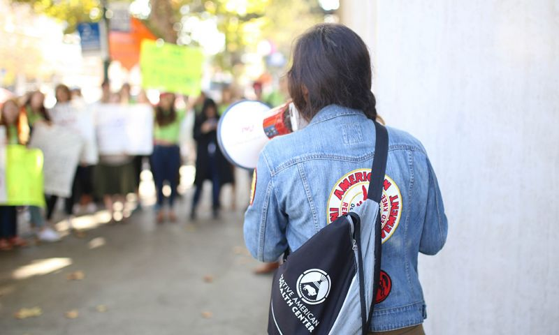 A young leader speaks into a bullhorn with their back turned to the camera. Protestors can be seen in the background.